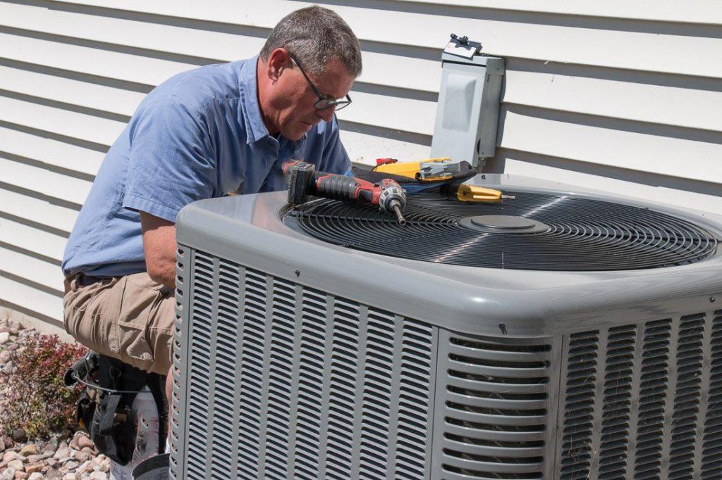 Technician repairing central air conditioner